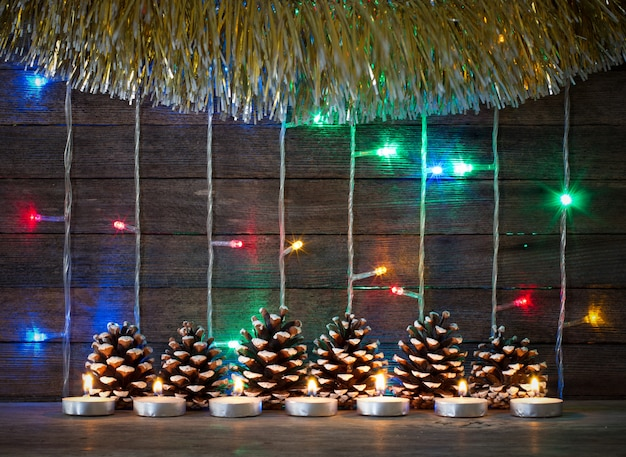 Colorful lights of garlands, fir cones and candles