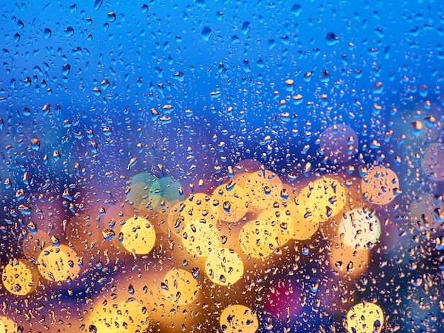 Colorful lights of the night city through the wet glass
