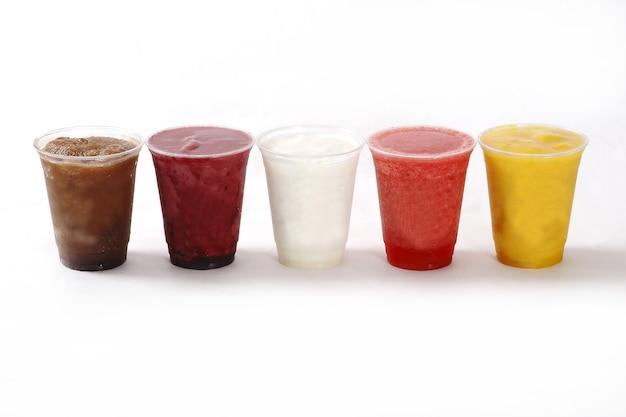 白い表面のプラスチックカップのさまざまなスムージーのカラフルなライン