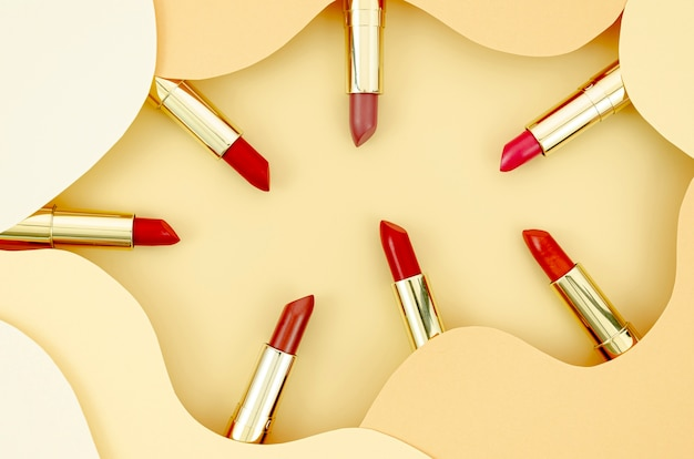 Colorful lipsticks on beige background