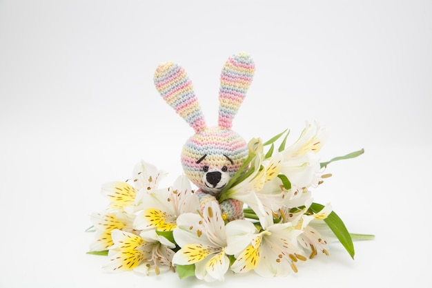 Colorful little hare with white flowers, handmade, knitted toy, amigurumi