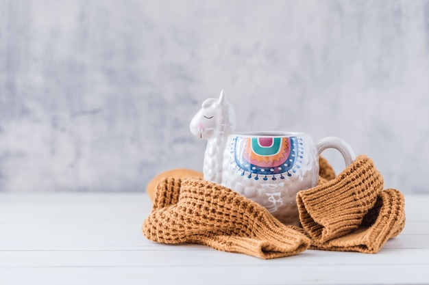 Colorful llama shaped mug with knitted pullover on the white wooden table