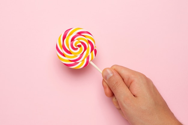 Colorful lollipop in hand on pink