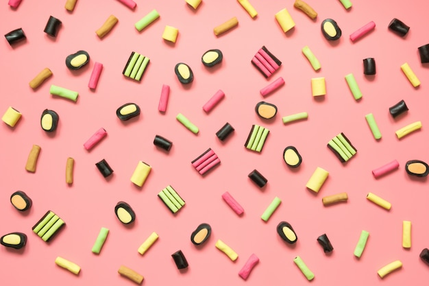 Colorful lollipop and licorice candy on pink.