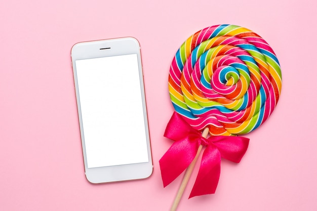 Colorful lollipop and mobile phone on pink