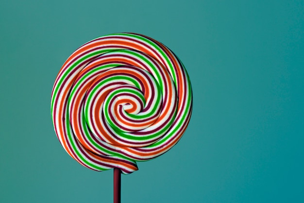 Colorful lollipop in spiral shape on green background