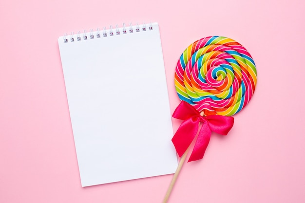 Colorful lollipop with notebook on pink