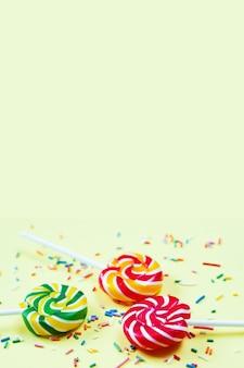 黄色の背景にカラフルなロリポップと紙吹雪。パーティーのお菓子。シュガー