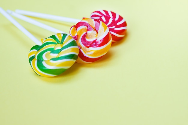 Colorful lollipops and confetti on yellow