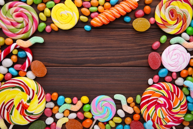 Colorful lollipops and different colored round candy on brown background