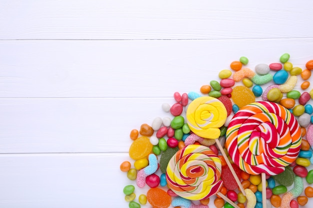 Colorful lollipops and different colored round candy on white background