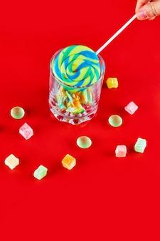 Lecca-lecca colorati nel bicchiere vuoto con caramelle sulla superficie rossa.