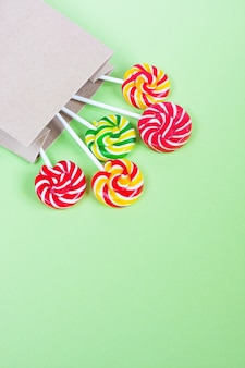 Colorful lollipops in paper bag on green background.