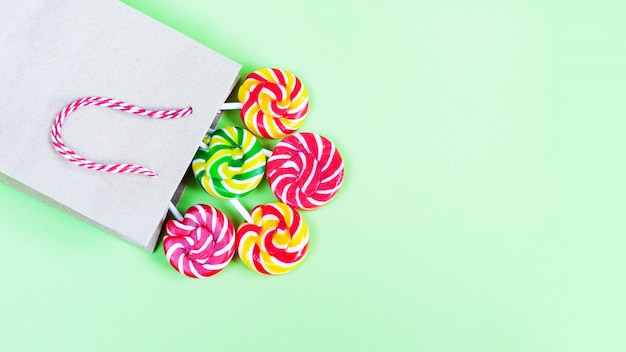 Colorful lollipops in paper bag on green