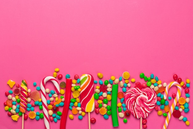 Colorful lollipops on a pink background