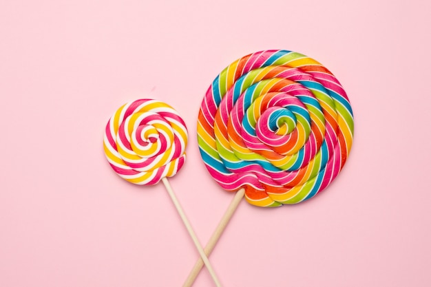Colorful lollipops spiral with wooden stick on pink