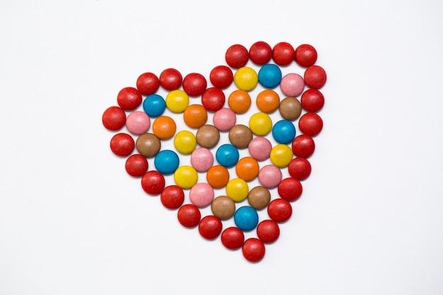 흰색 바탕에 사랑 모양에 화려한 m & m 버튼 초콜릿 사탕.