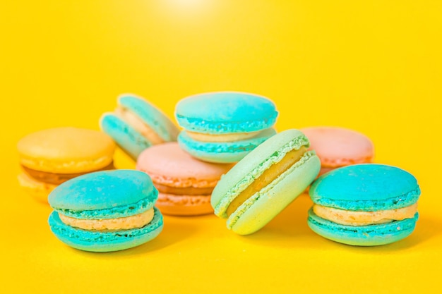 Colorful macaron dessert cake isolated on yellow table