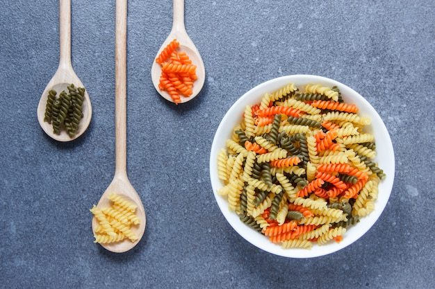 Colorful macaroni pasta in a bowl and spoons top view on a gray surface