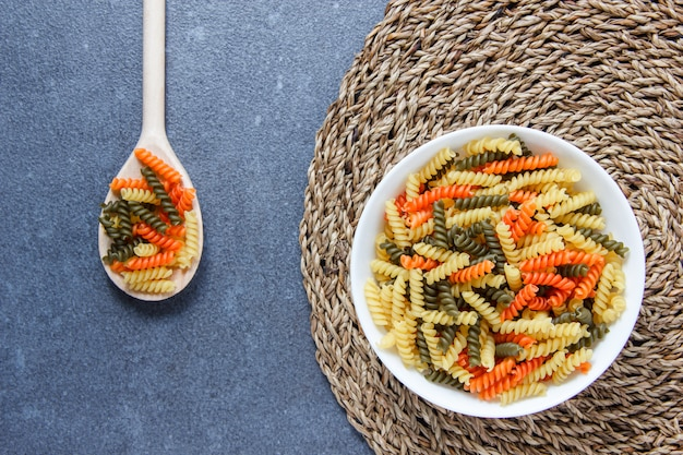 Colorful macaroni pasta in a bowl and spoons on a trivet and gray surface. top view.