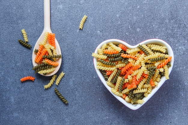 Colorful macaroni pasta in a heart shaped bowl and spoon on a gray surface
