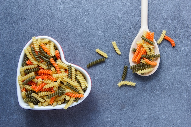 Colorful macaroni pasta in a heart shaped bowl and spoon top view on a gray surface