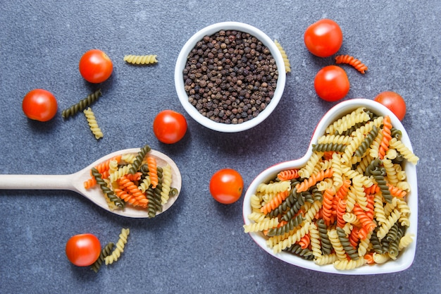 Colorful macaroni pasta in a heart shaped bowl and spoon with tomatoes, black pepper top view on a gray surface