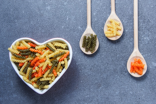 Colorful macaroni pasta in a heart shaped bowl and spoons on a gray textured surface