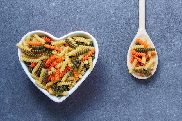 Красочные макароны макарон в миску и ложку в форме сердца на серой поверхности
