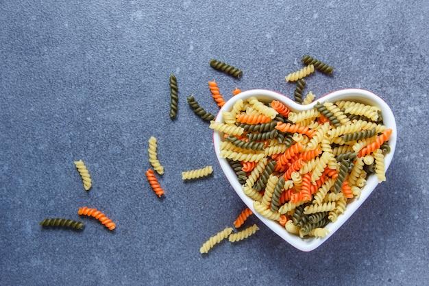 Красочные макароны макароны в миску в форме сердца на серой поверхности