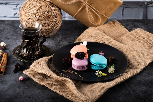Colorful macarons in a black saucer and a glass of tea on a black table