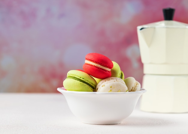 Colorful macarons cookies in white bowl on pastel background, copy space.
