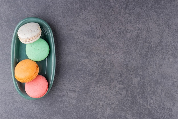 Dessert colorato macarons posto su un tavolo di pietra.