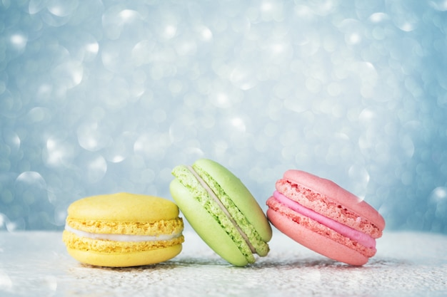 Colorful macarons on light blue glitter bokeh background