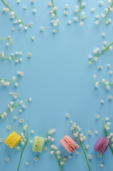 Colorful macarons or macaroons decorated with blooming lily of the valley flowers on pastel blue background. sweet french dessert concept. frame composition. flat lay. vertical