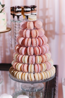 Colorful macarons stand in round transparent weight as part of candy bar sweet table