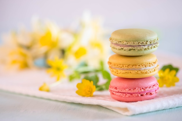Colorful macarons on towel with flowers and narcissus