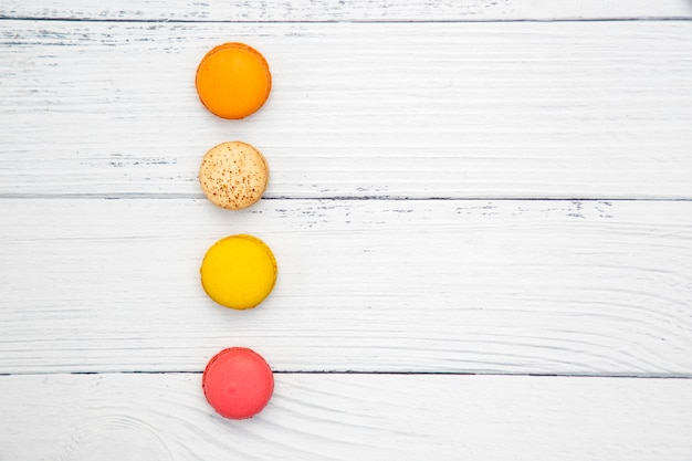 Colorful macarons on white wooden background