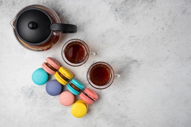 Macarons colorati con tazza da tè e due tazze di tè nero su sfondo bianco.
