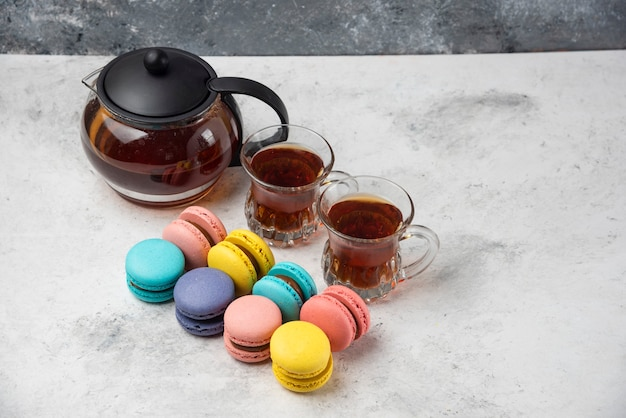 Colorful macarons with teacup and two cups of black tea on white surface.