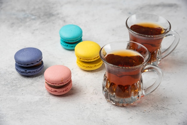Colorful macarons with two cups of black tea on white surface.