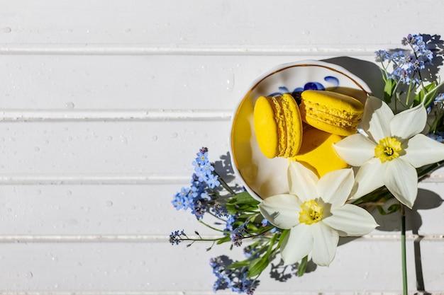 Красочные миндальное печенье и цветы на белом деревянном столе, вид сверху сладкого миндального печенья с копией пространства для вашего текста, вкусного десерта и цветов нарциссов и забывчивых цветов