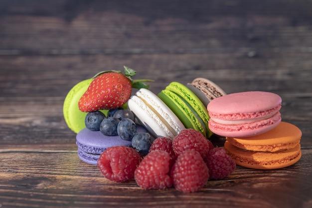 Красочные миндальное печенье и лесные ягоды стоят на деревянной поверхности