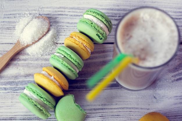 Разноцветные миндальное печенье укладываются в ряд и латте в стакане