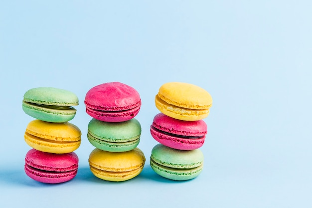 Colorful macaroons on a blue copyspace, close-up, flatley with copyspace