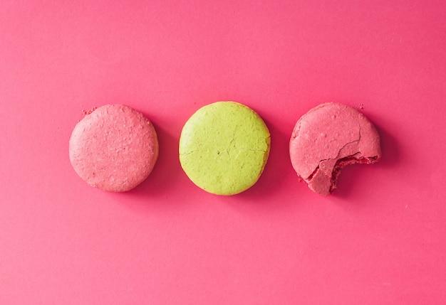 ピンクの壁にカラフルなマカロンケーキ。フラットレイ。