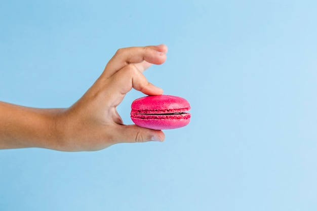 Colorful macaroons in a child's hand on a blue copyspace, close-up, flatley with copyspace