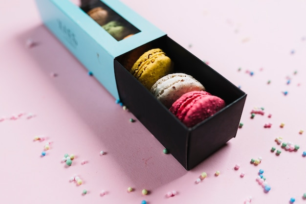 Colorful macaroons cookies in a box on a pink background