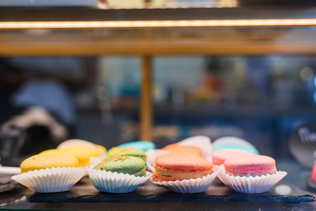 Colorful macaroons in the cupcake paper holder inside the display cabinet