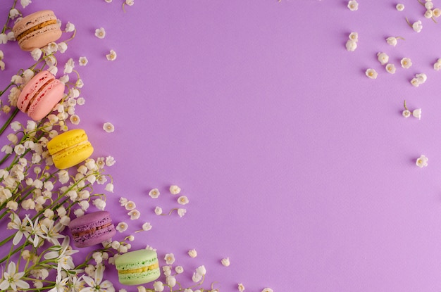 Colorful macaroons decorated with blooming lily of the valley on purple background. sweet french dessert concept. frame composition. flat lay. copyspace. greeting card concept